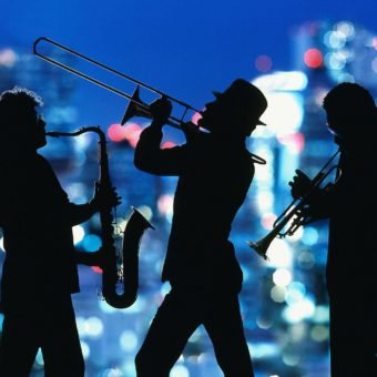 silhouette of jazz musicians against a city backdrop