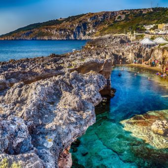 People swimming in a rocky cove in Puglia, Italy